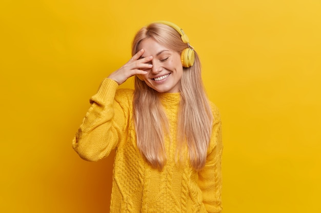 Schüchterne positive blonde frau lächelt breit schließt die augen genießt es, lieblingsmusik über drahtlose kopfhörer zu hören