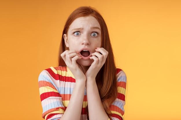 Schüchterne unsichere junge ingwer mädchen blaue augen fühlen sich ängstlich nach luft schnappen schockiert erschrocken zitternde angst halten finger mund stirnrunzelnde grimasse starren kamera stupor erschrocken, ängstlich ausflippen.