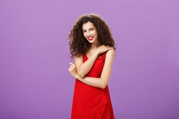 Schüchterne weibliche elegante europäische frau mit lockiger frisur und lippenstift in rotem luxuriösem kleid...
