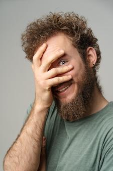 Schüchterner hübscher junger mann bedeckte sein gesicht mit hand, der mit seinem auge hebelt, lockiges haar im olivgrünen t-shirt, das auf weißer wand isoliert wird
