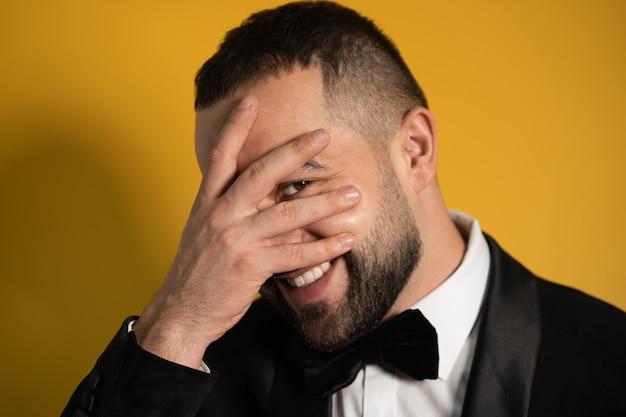 Schüchterner junger bärtiger mann im smokingfell guckt mit geschlossenen augen hinter seinen händen hervor. hübscher junger lächelnder kaukasischer mann lokalisiert auf gelbem hintergrund.
