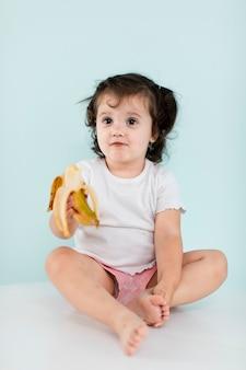 Schüchternes baby, das eine banane hält