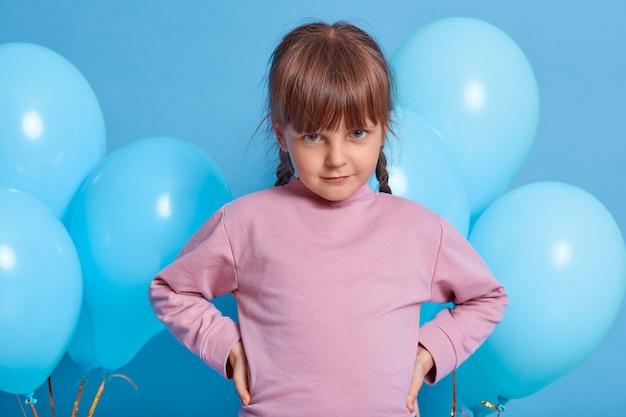 Schüchternes entzückendes kleines kindermädchen, das mit blauen luftballons über farbhintergrund lokalisiert aufwirft. schönes kind, das kamera unter der stirn betrachtet, hände auf den hüften hält und rosenpullover trägt.