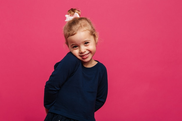 Schüchternes junges blondes mädchen, welches die kamera über rosa wand aufwirft und betrachtet