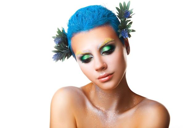 Schüchternes junges mädchen mit blumen im haar und mehrfarbigem make-up studioaufnahme isoliert