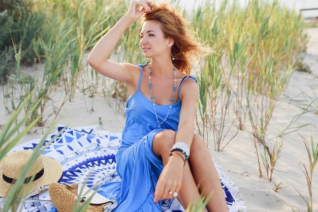 Schüchternes mädchen mit perfekter bräunungshaut, die auf sonnigem strand im trendigen blauen kleid auf sand sitzend aufwirft. windige haare. abendsonnenlicht.