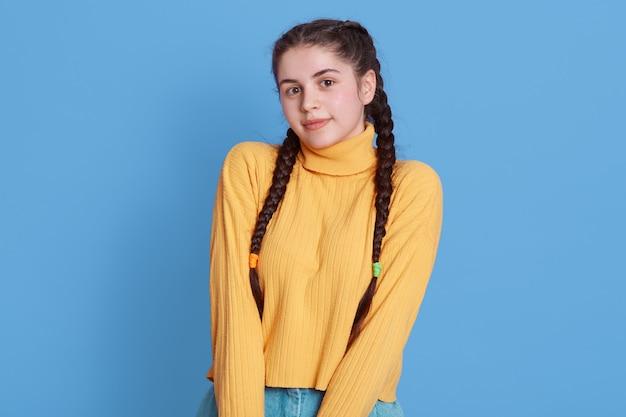 Schüchternes mädchen mit zöpfen im lässigen outfit, steht lächelnd isoliert auf lebendiger blauer farbwand, trägt gelben lässigen pullover und schaut nach vorne