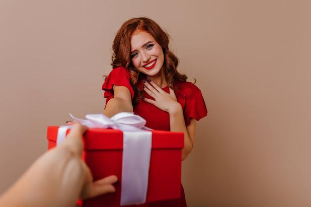 Schüchternes schönes mädchen im roten kleid, das in ihrem geburtstag aufwirft. innenfoto der lockigen inspirierten frau mit neujahrsgeschenk.