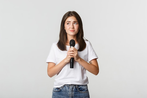 Schüchternes süßes brünettes mädchen, das angst hat, in der öffentlichkeit zu singen, mit mikrofon zu stehen und nervös auszusehen.