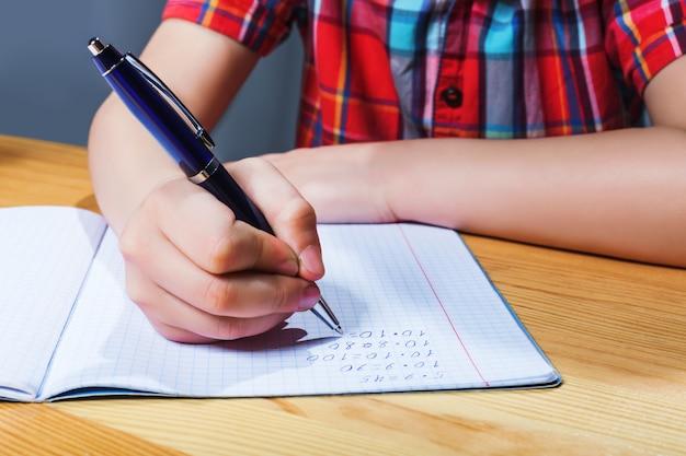 Schüler am schreibtisch schreiben in der notizbuch-nahaufnahme