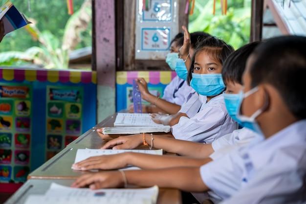 Schüler asiatischer kinder tragen gesichtsmasken, die im klassenzimmer der grundschule lernen. schüler heben ihre hände, um fragen zu beantworten, die lehrer ihnen stellen