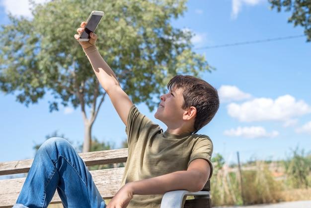 Schüler auf der bank, die pause unter verwendung des mobiles macht