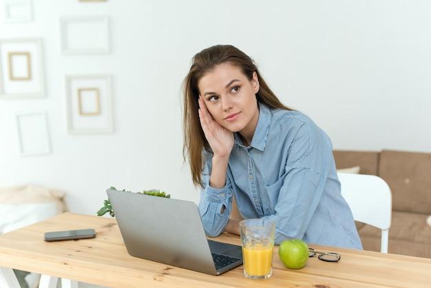 Schüler denken, während sie komplizierte hausaufgaben online mit einem laptop zu hause erledigen. foto der jungen hübschen geschäftsfrau sitzen drinnen im büro mit laptop-computer, die nachdenklich in die luft starrt.