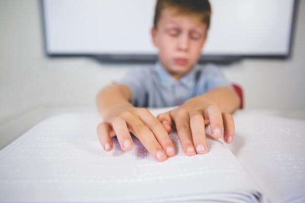 Schüler, der ein braillebuch im klassenzimmer liest