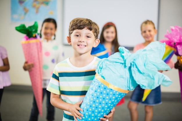 Schüler, der geschenk im klassenzimmer hält