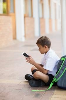 Schüler, der im korridor sitzt und digitale tablette verwendet
