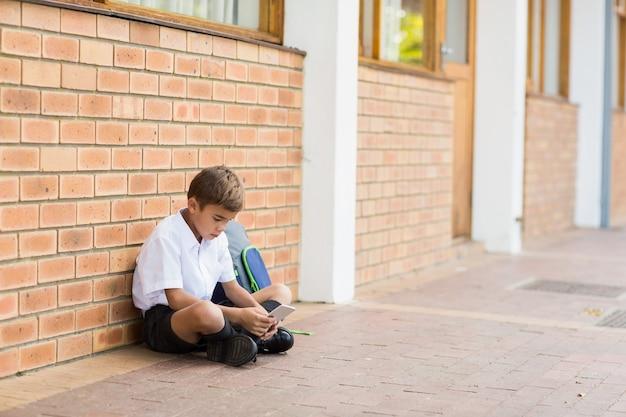Schüler, der im korridor sitzt und handy verwendet
