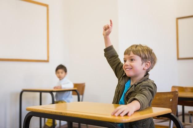 Schüler, der seine hand an seinem schreibtisch anhebt