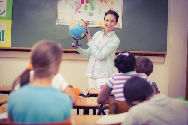 Schüler, die auf ihren lehrer halten, der kugel hält