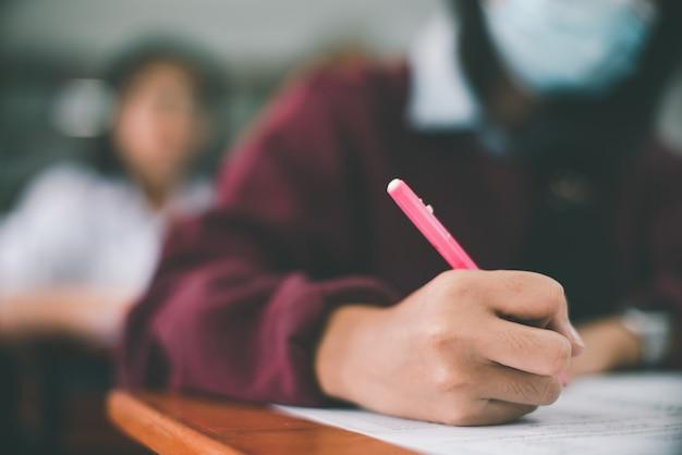 Schüler, die eine maske zum schutz des corona-virus oder covid-19 tragen und eine prüfung im klassenzimmer mit stress durchführen