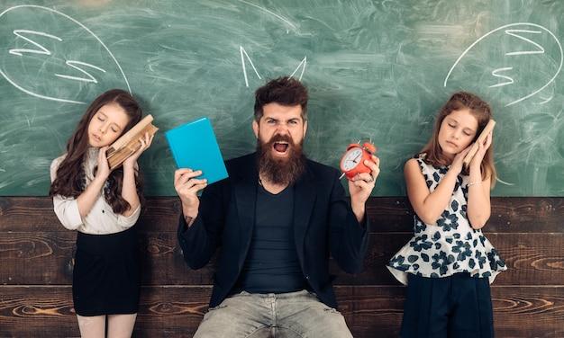 Schüler, die es satt haben, in der schule zu lernen. lehrer schreien schläfrige schüler an. tutor mit wecker und buch. zeit, konzept zu lernen.