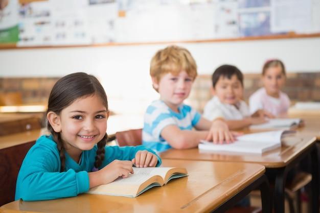 Schüler, die in den klassenzimmerlesebüchern sitzen
