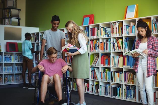 Schüler, die in der bibliothek miteinander interagieren