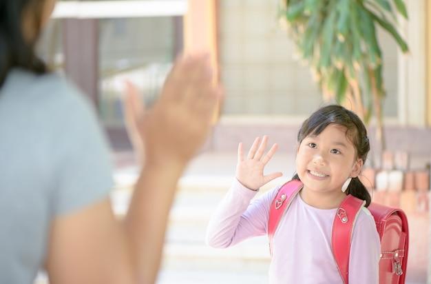 Schüler gehen zur schule und winken zum abschied