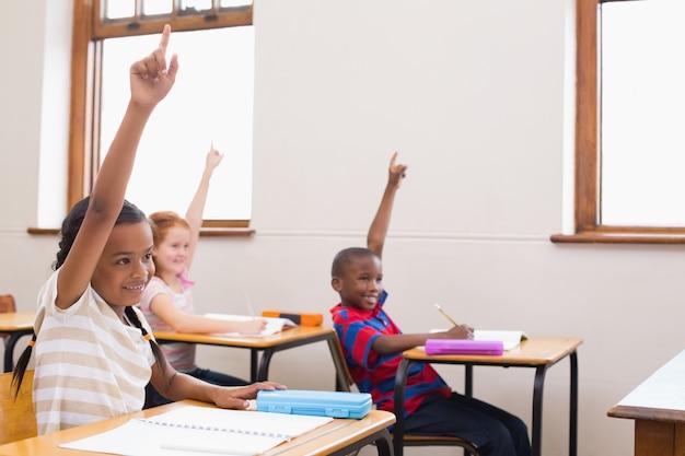 Schüler heben ihre hände während des unterrichts