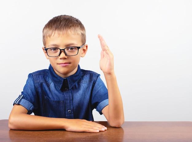 Schüler in einem blauen hemd, das am tisch sitzt. junge mit brille
