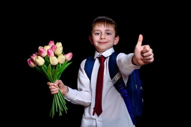 Schüler in einem hemd mit der bindung und schultasche, die einen blumenstrauß von tulpen für muttertag halten