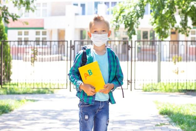 Schüler in einer schutzmaske mit einem rucksack und einem lehrbuch in den händen