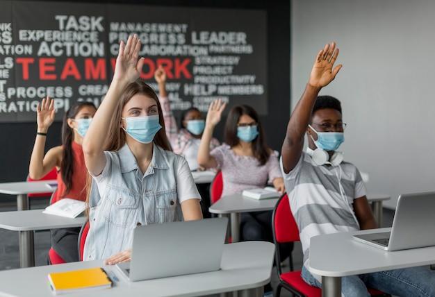 Schüler mit mittlerem schuss und erhobenen händen