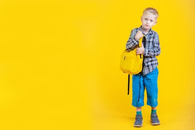 Schüler mit rucksack auf gelbem hintergrund