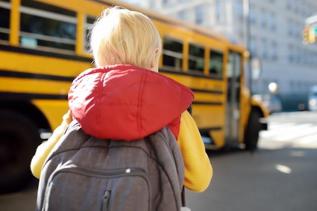 Schüler mit schultasche mit gelbem schulbus