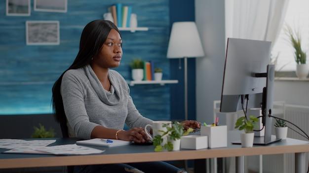 Schüler mit schwarzer haut, der nach online-kursen sucht, die schulhausaufgaben auf dem computer schreiben