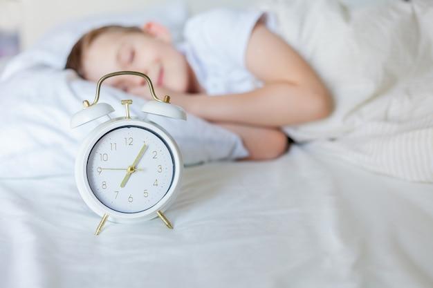 Schüler mit wecker, der im bett schläft. morgen.