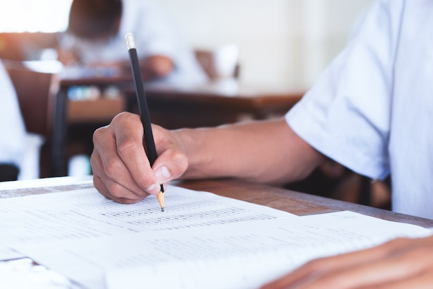 Schüler nimmt prüfung und schreibt antwort in klassenzimmer für bildungstestkonzept.