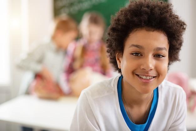 Schüler. porträt eines freudigen netten schuljungen, der lächelt, während er sie ansieht