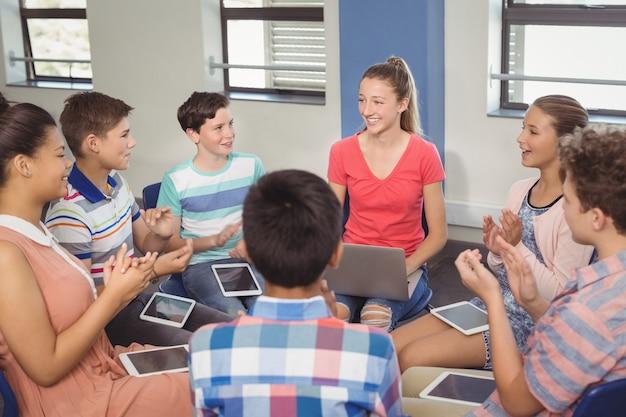 Schüler schätzen klassenkameraden nach der präsentation im klassenzimmer