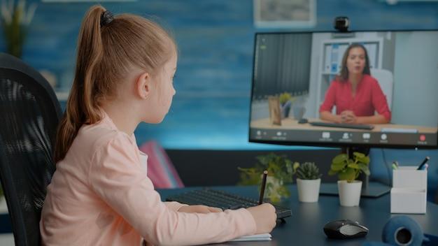 Schüler schreiben auf lehrbuch und sprechen mit dem lehrer per videoanruf