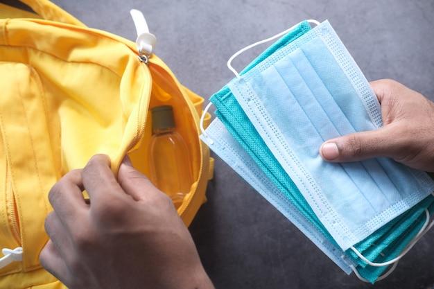 Schüler-schultaschenpackung mit desinfektionsmittel und gesichtsmaske.