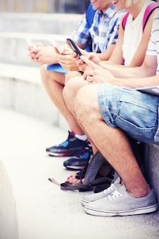 Schüler sitzen mit ihren smartphones auf treppen stairs