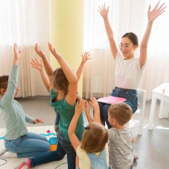 Schüler spielen mit ihrer kindergärtnerin ein spiel