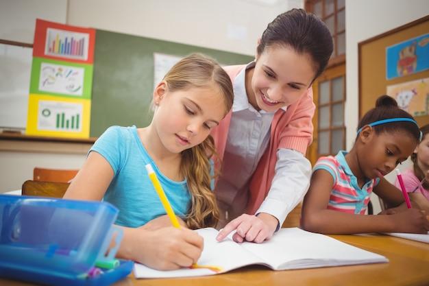 Schüler und lehrer am schreibtisch im klassenzimmer in der grundschule