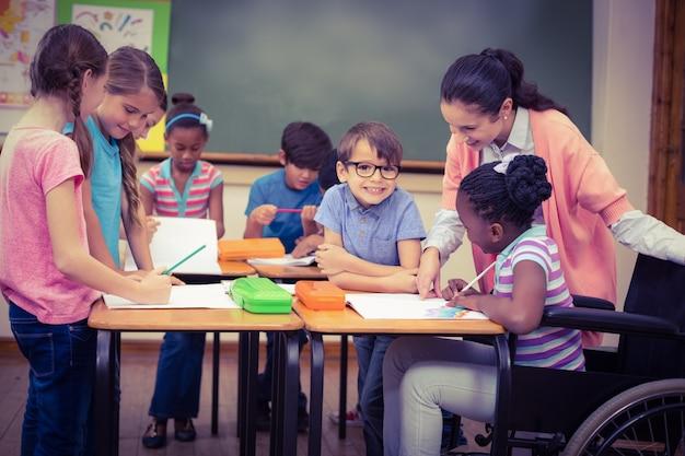 Schüler und lehrer arbeiten am schreibtisch zusammen