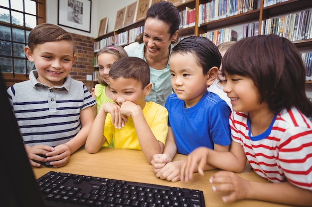 Schüler und lehrer in der bibliothek mit computer
