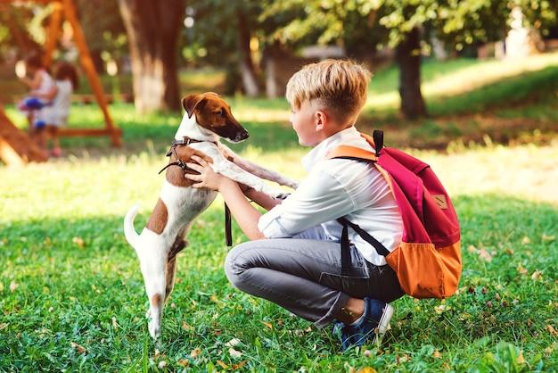 Schüler und sein hund gehen im park spazieren. freundschaft, tiere und lebensstil. junge mit jack russell terrier im freien. glücklicher kerl, der mit hund auf grünem gras spielt.