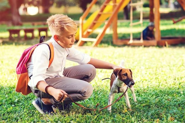 Schüler und sein hund gehen im park spazieren. freundschaft, tiere und lebensstil.