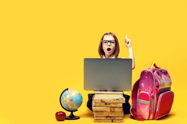 Schüler unter schock sitzt hinter einem stapel bücher und laptop und hebt den zeigefinger kindererziehung